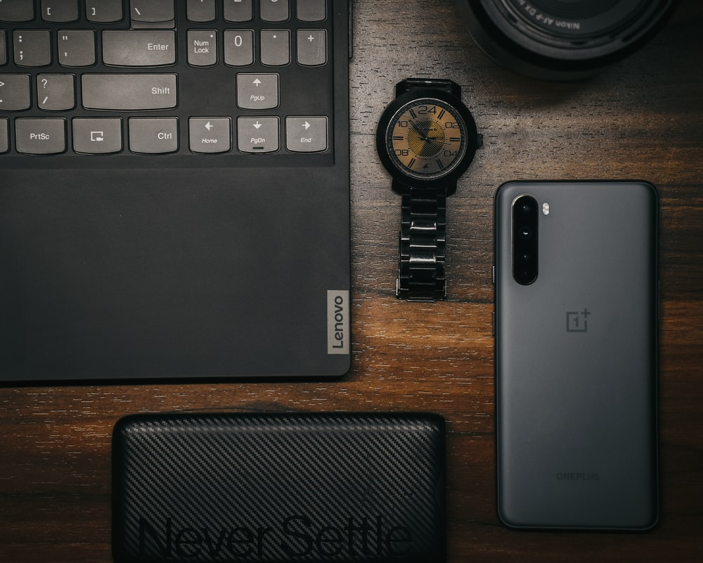 black and silver laptop computer beside black round watch on brown wooden table