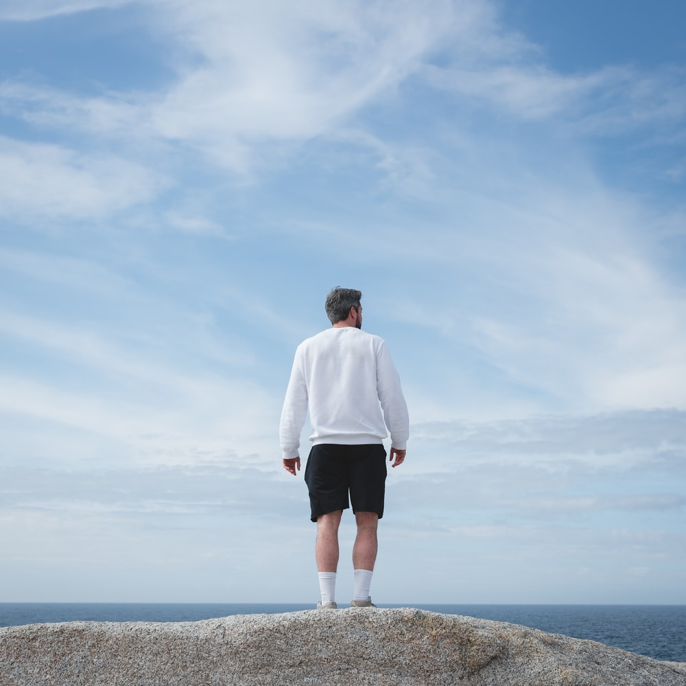 man in white long sleeve shirt and black shorts standing on gray rock formation during daytime