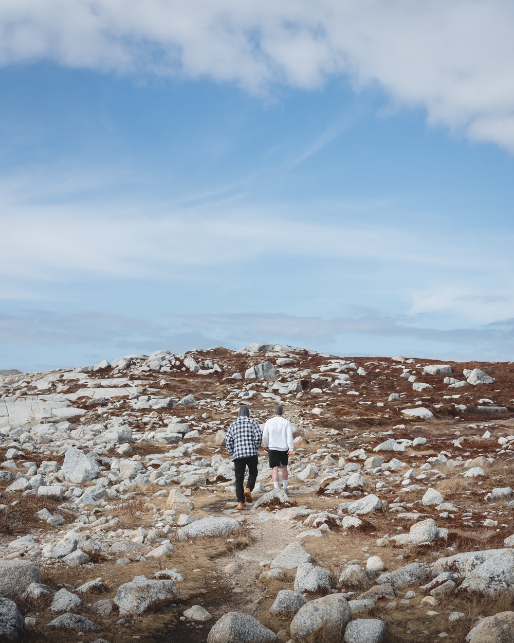 man and woman walking on rocky hill under blue sky during daytime