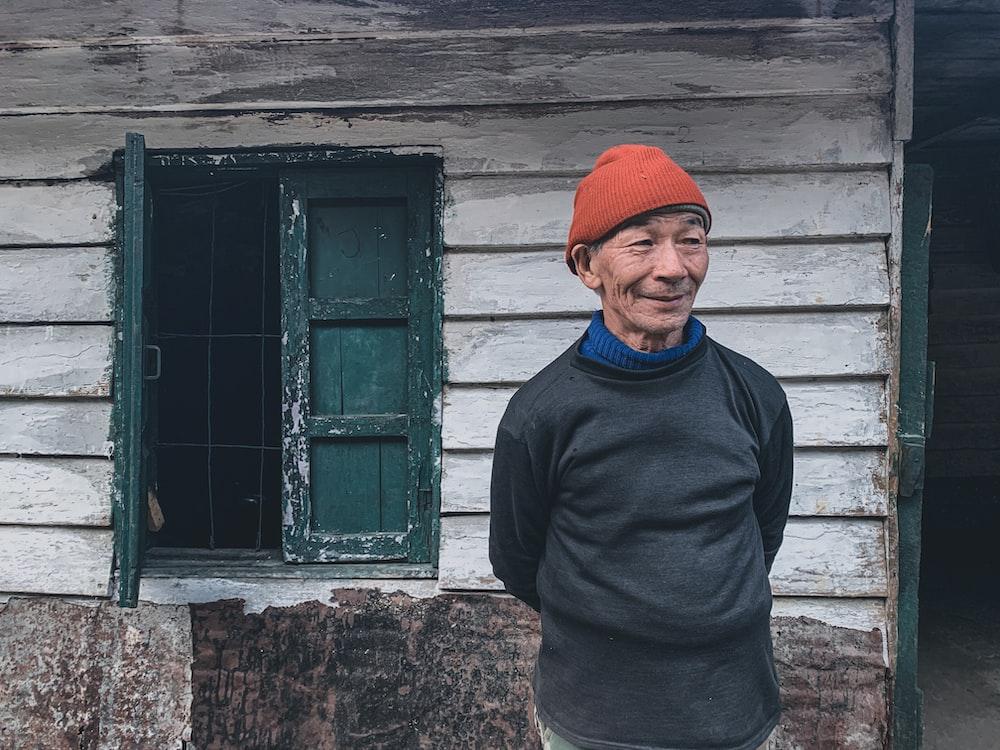 man in black sweater standing beside green wooden window