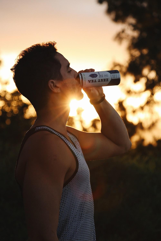 woman in black tank top drinking from bottle