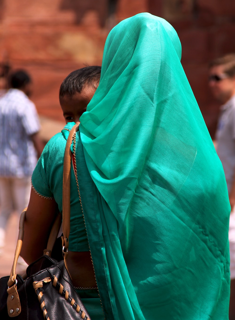 woman in teal hijab standing near people during daytime