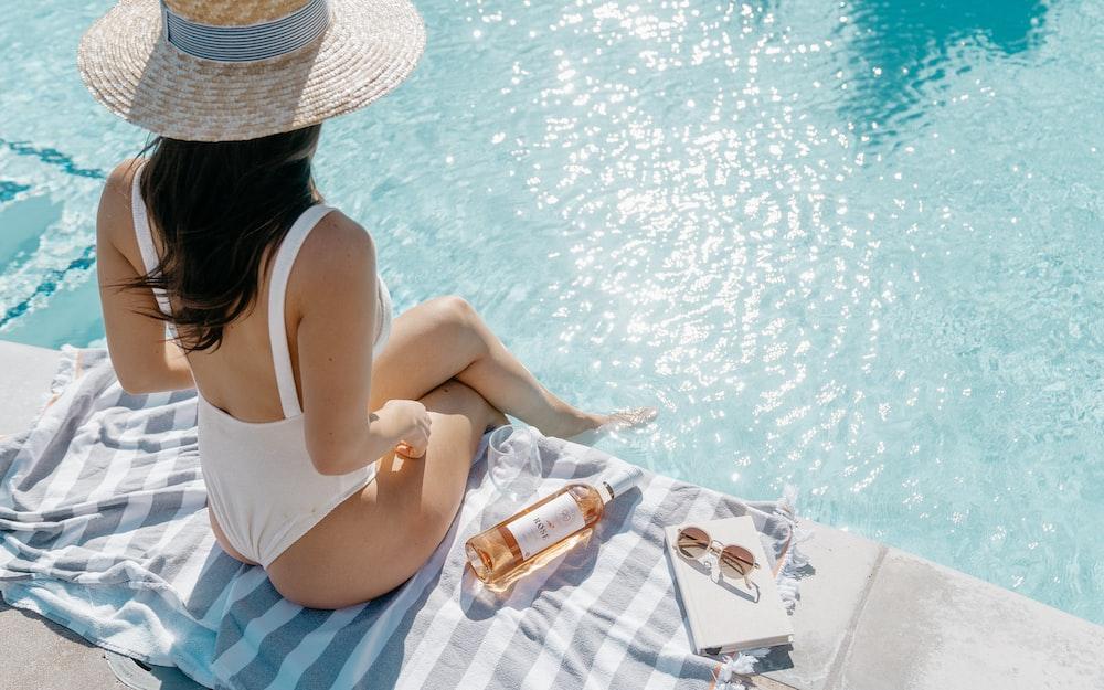 woman in white bikini lying on white and blue stripe towel on swimming pool during daytime