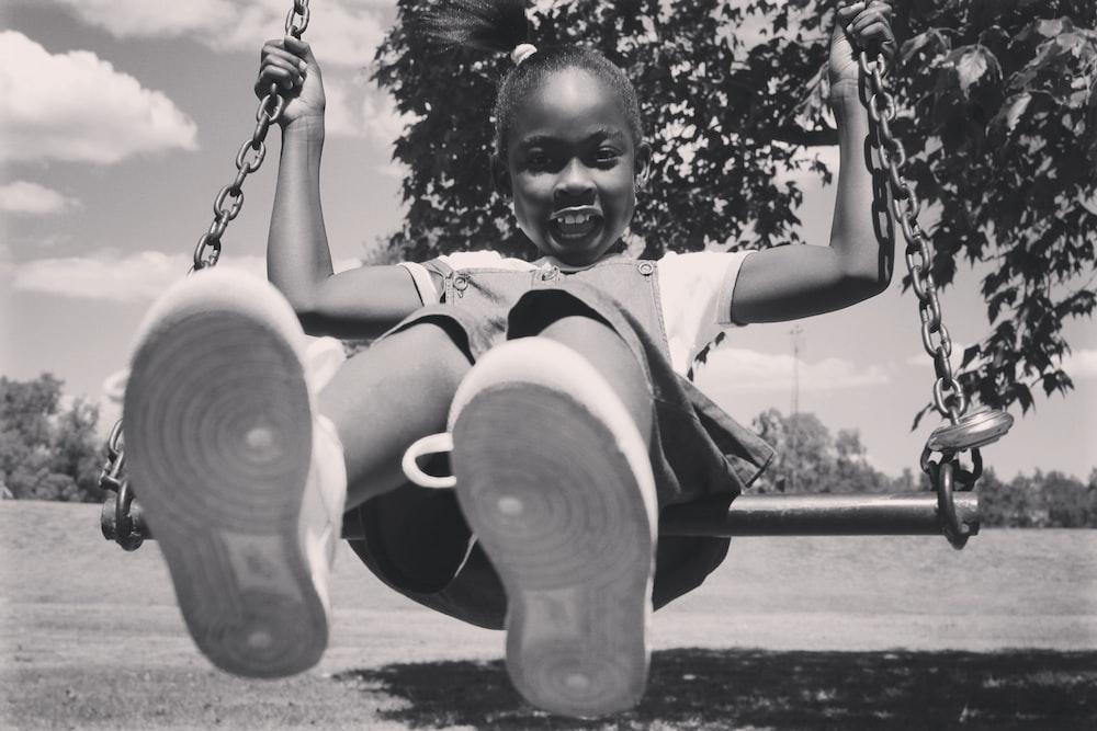 grayscale photo of girl sitting on swing