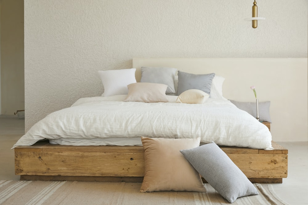 white bed pillow on brown wooden bed frame