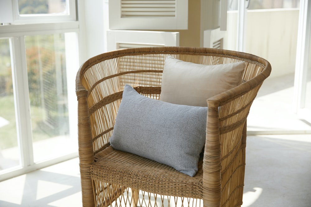 brown wicker armchair with gray throw pillow