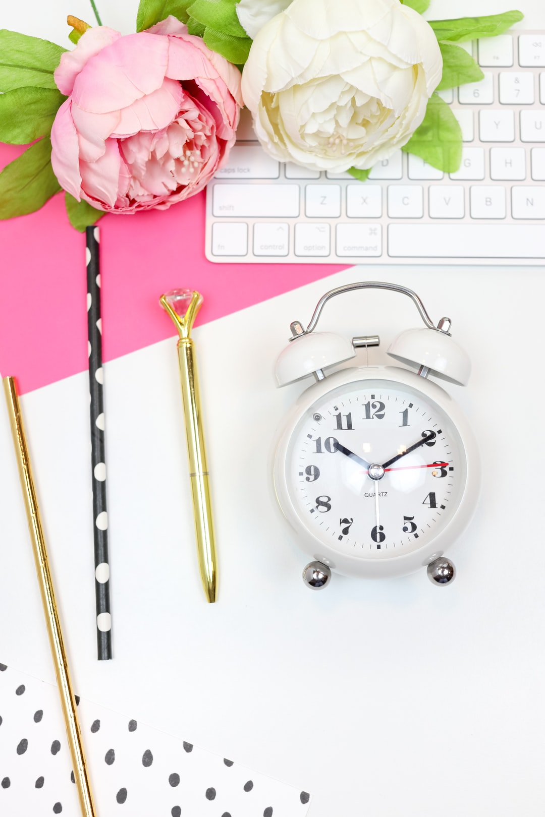 This feminine styled stock photo perfect for lady bosses features hot pink and black props with a white desk, a keyboard, pink and black notecards, pens, a clock, and more.