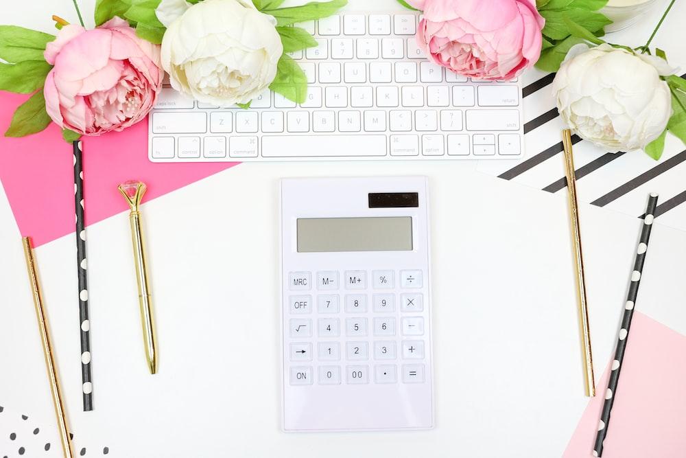 white calculator beside pink rose
