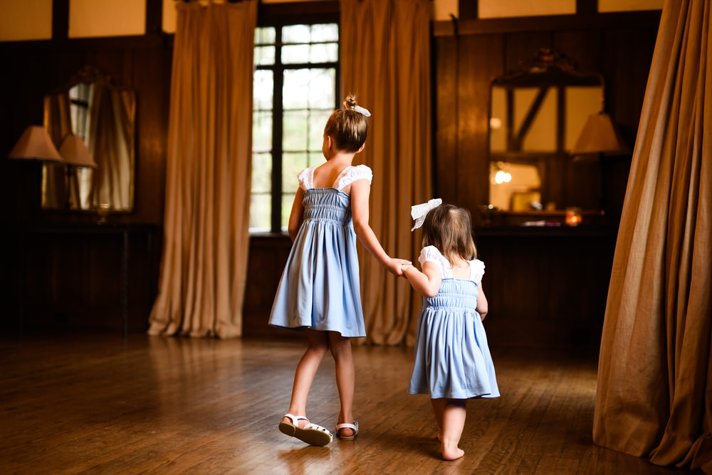 girl in blue and white stripe dress standing on brown wooden floor