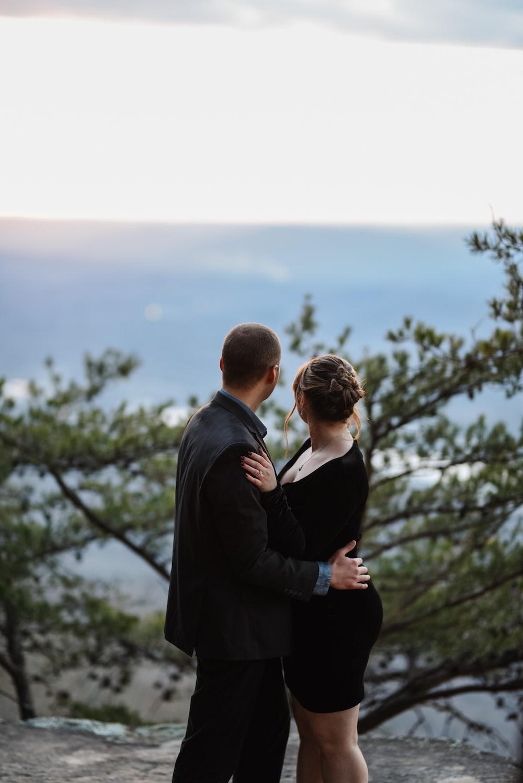 man in black suit standing in front of woman in black blazer