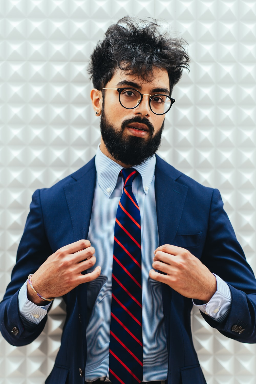 man in blue suit wearing black framed eyeglasses