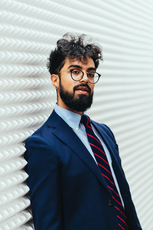 man in blue suit jacket wearing black framed eyeglasses