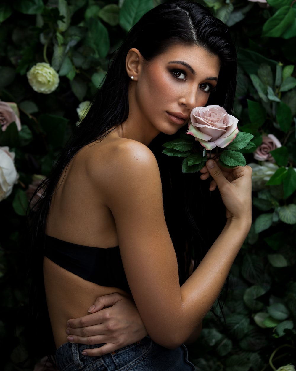 woman in black brassiere holding pink rose