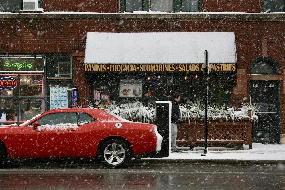 red sedan parked beside store during daytime