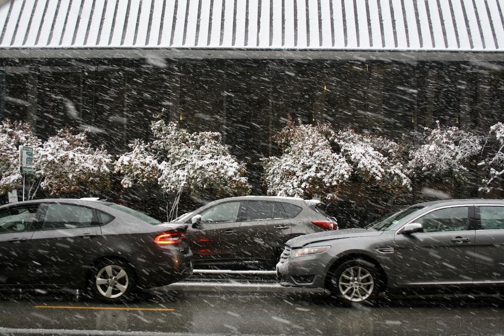 black sedan parked beside white building