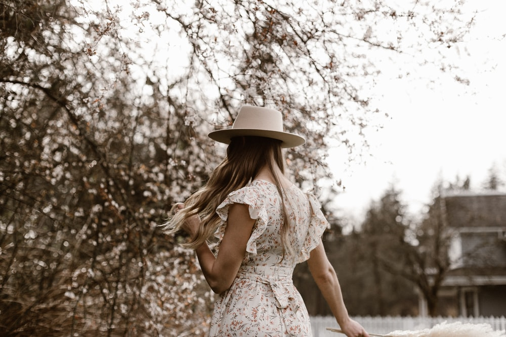 woman in white floral dress wearing white hat standing near trees during daytime
