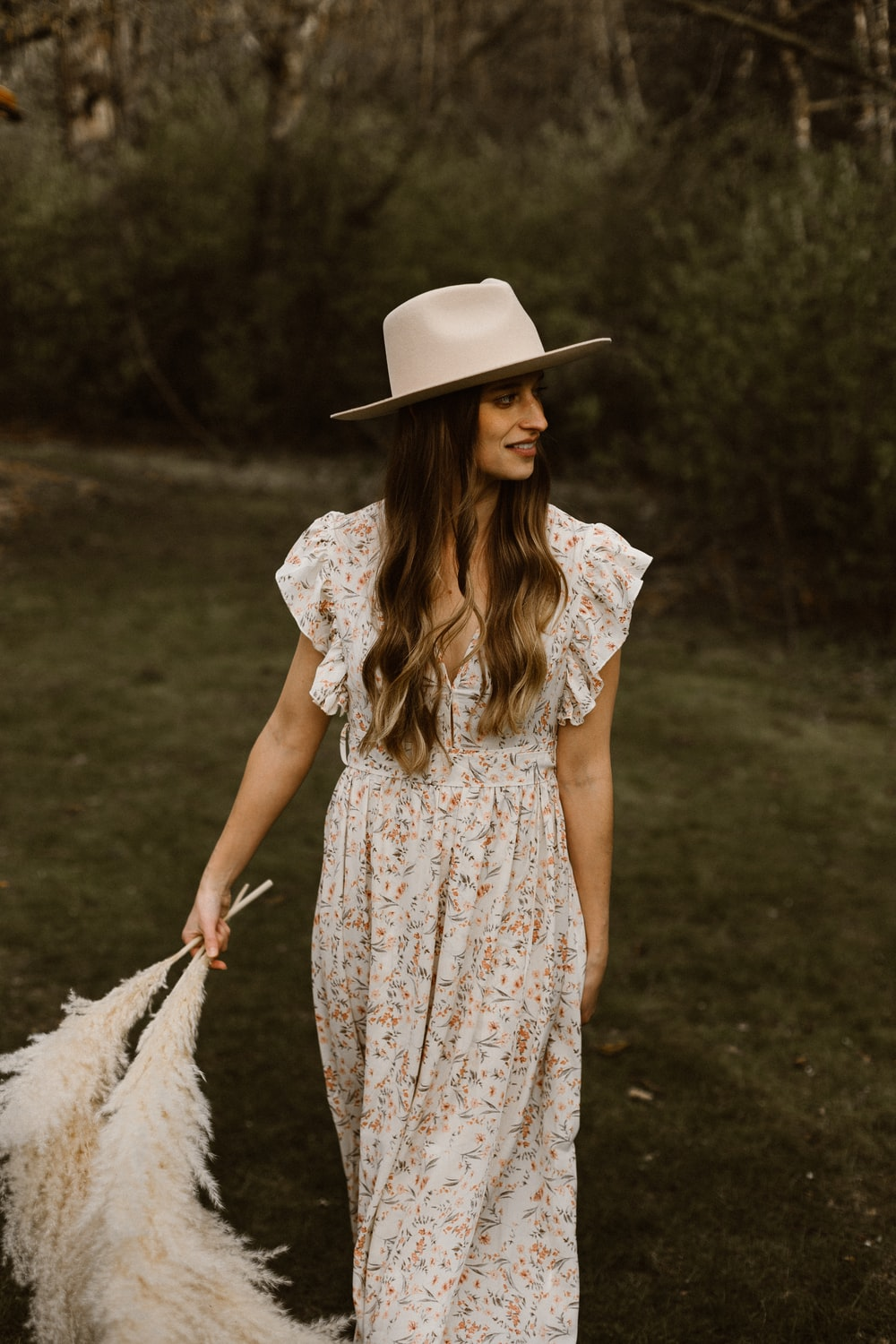woman in white and red floral dress wearing white sun hat