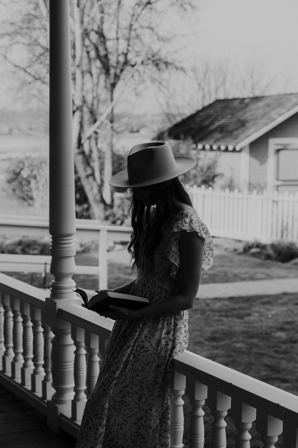 grayscale photo of woman in floral dress and hat sitting on wooden bench
