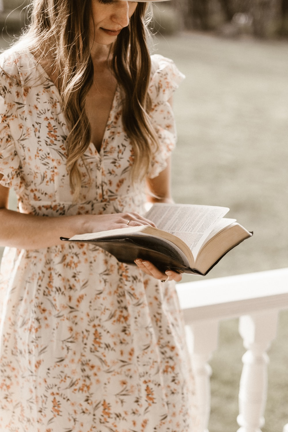 woman in white and brown floral dress reading book