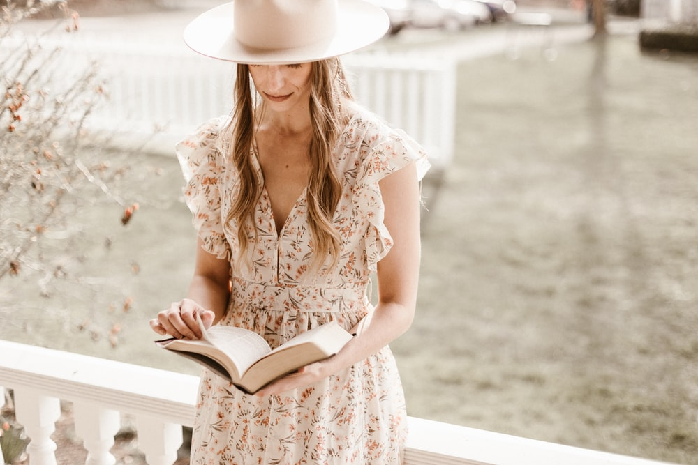 woman in white and brown floral dress wearing white hat