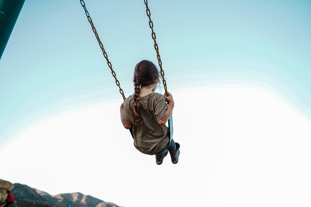 child in brown jacket sitting on swing during daytime