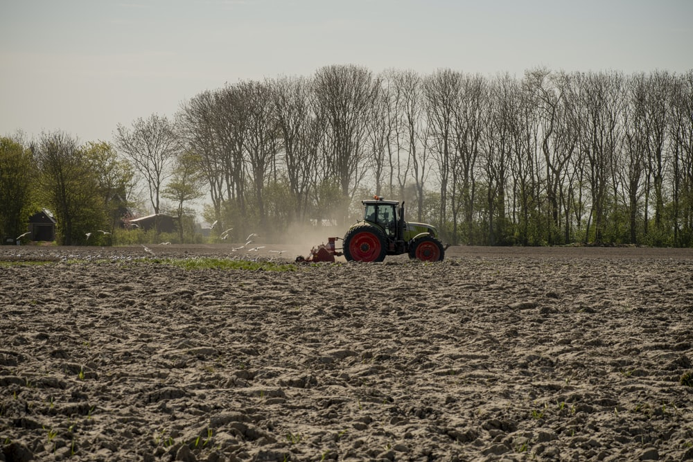 green and orange tractor on brown field during daytime