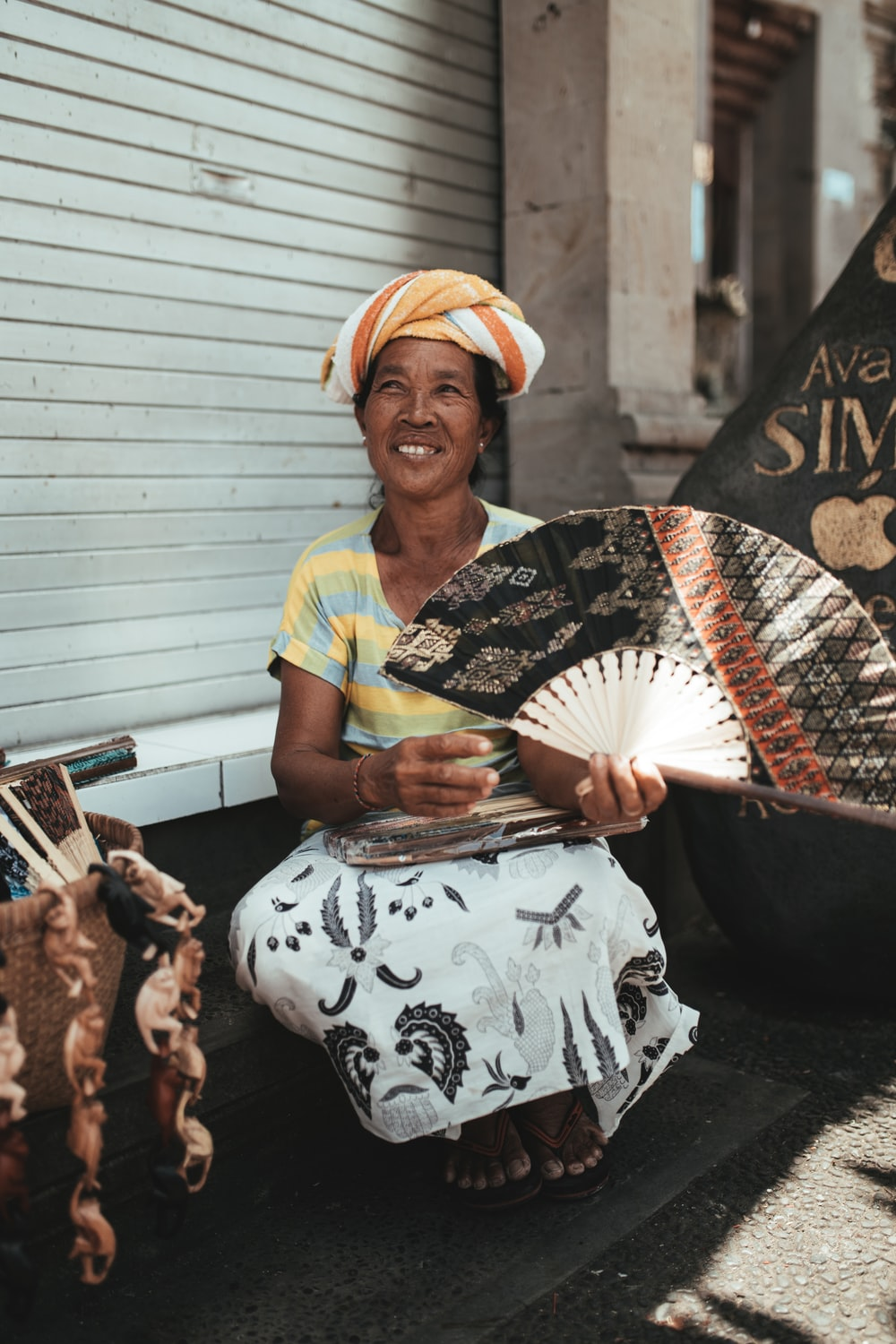 woman in yellow and black shirt holding white and black hand fan