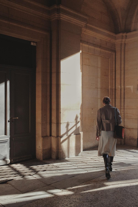 man in gray jacket walking on hallway