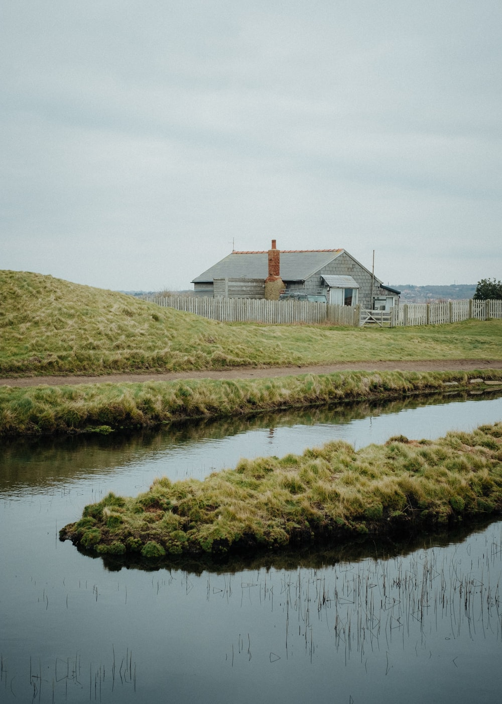 white and brown house near green grass and body of water during daytime