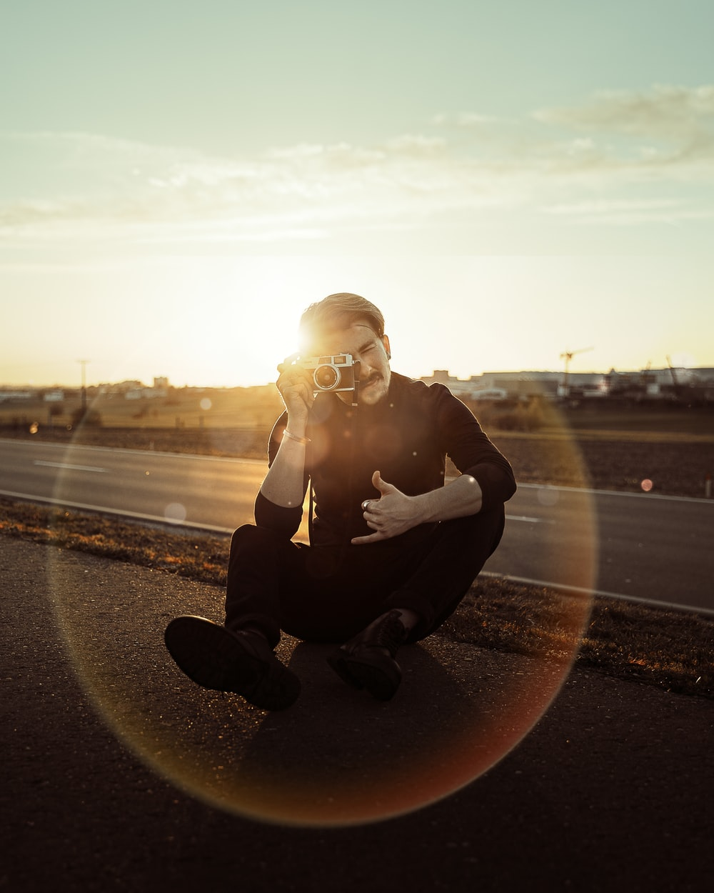 woman in black jacket sitting on road during sunset