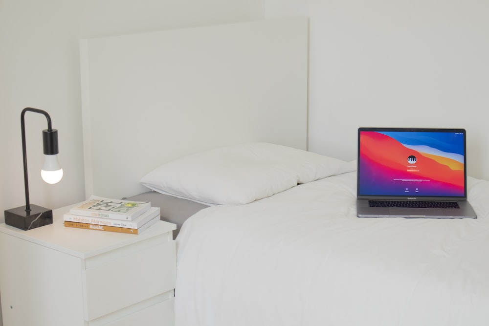 black laptop computer on white bed