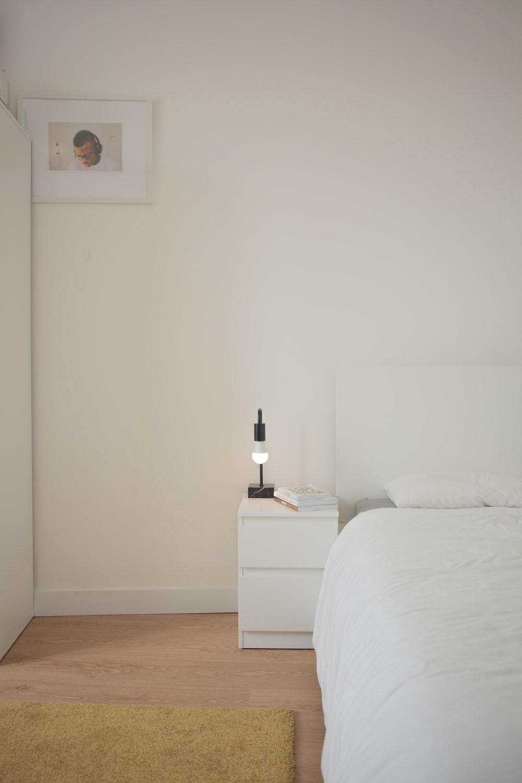 white bed linen beside white wooden nightstand