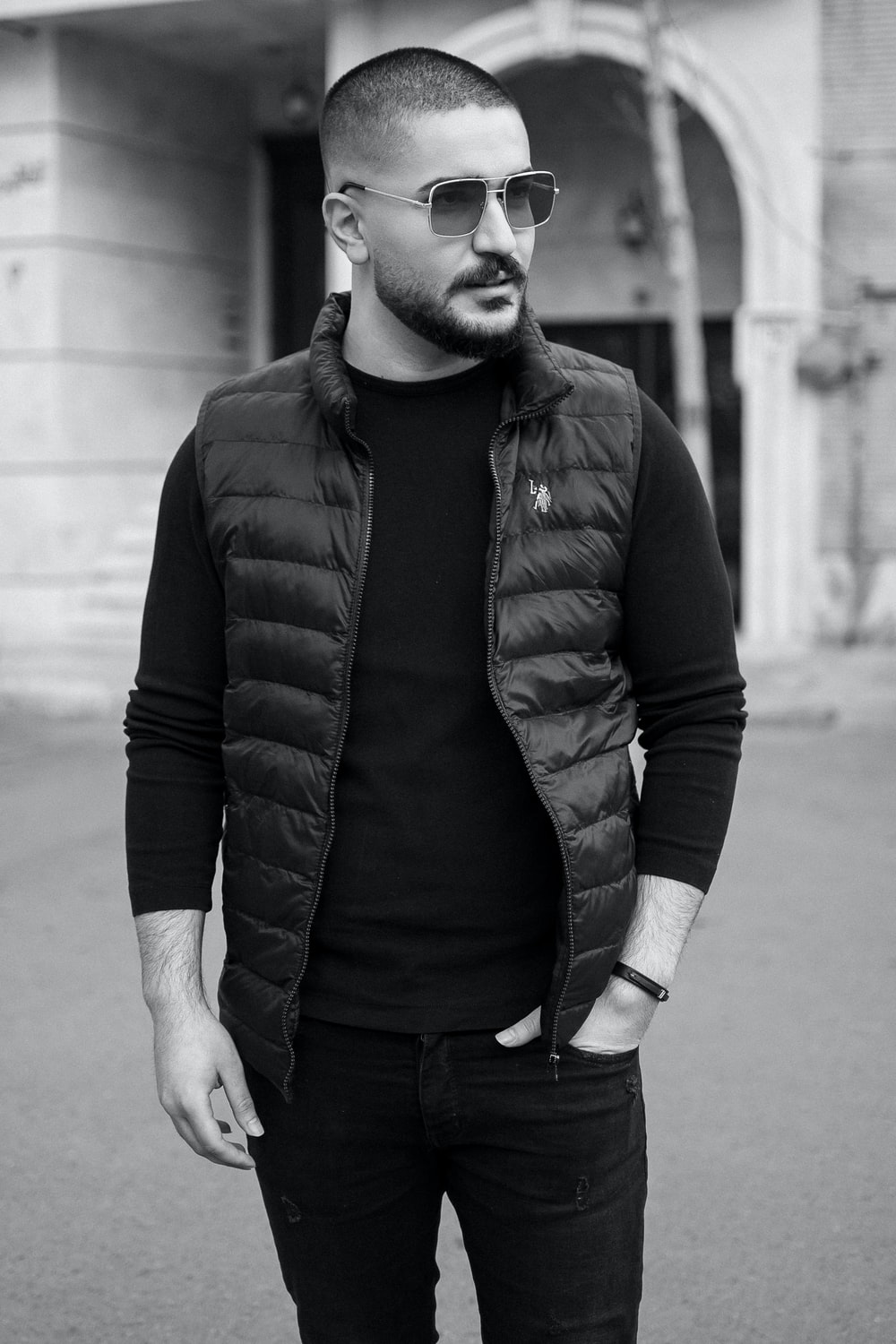 man in black jacket and black pants standing on sidewalk in grayscale photography