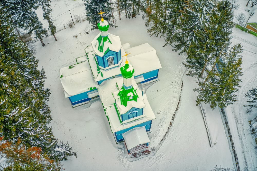 green and white snow covered house