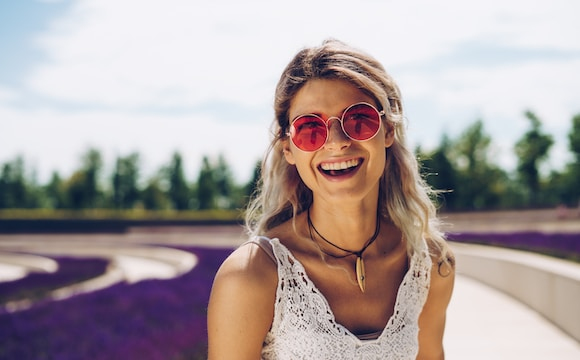 woman in white floral tank top wearing sunglasses