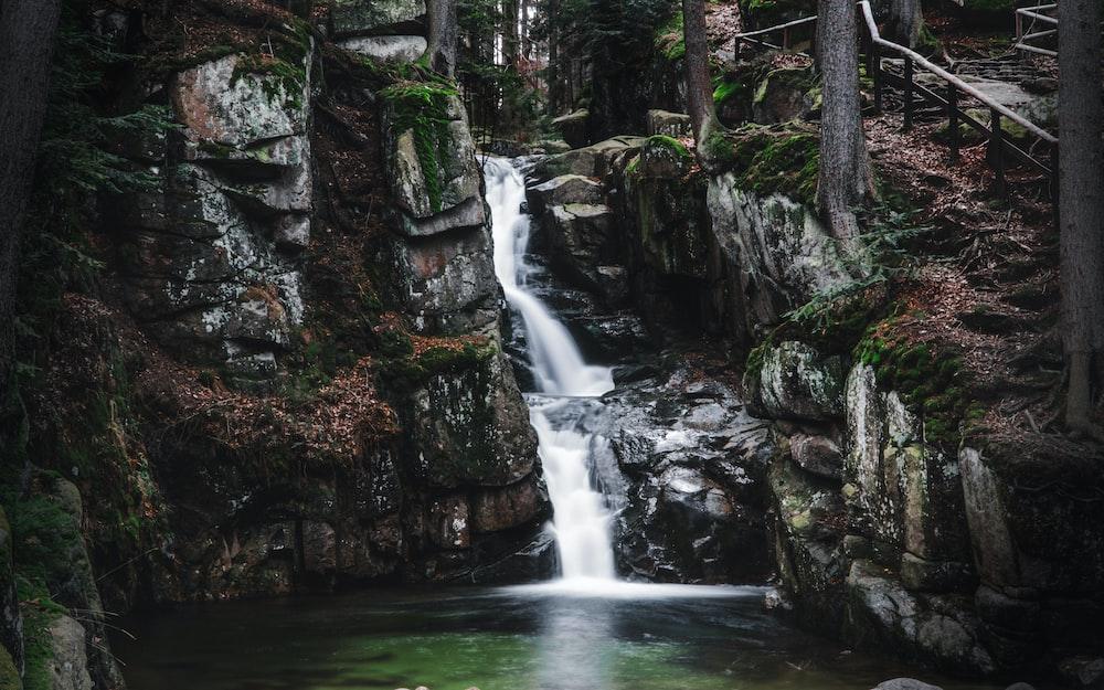 water falls between brown rocks