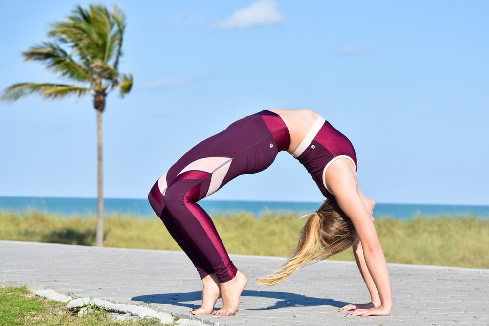 woman in black sports bra and purple leggings doing yoga on beach during daytime