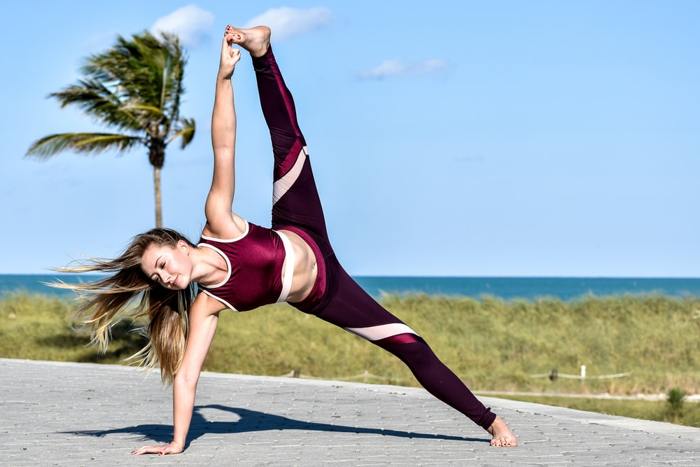 woman in red and black tank top and black leggings doing yoga during daytime