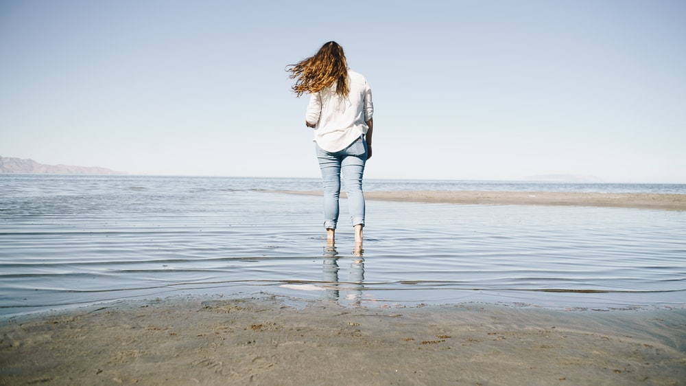 woman in white long sleeve shirt and blue denim jeans standing on beach during daytime