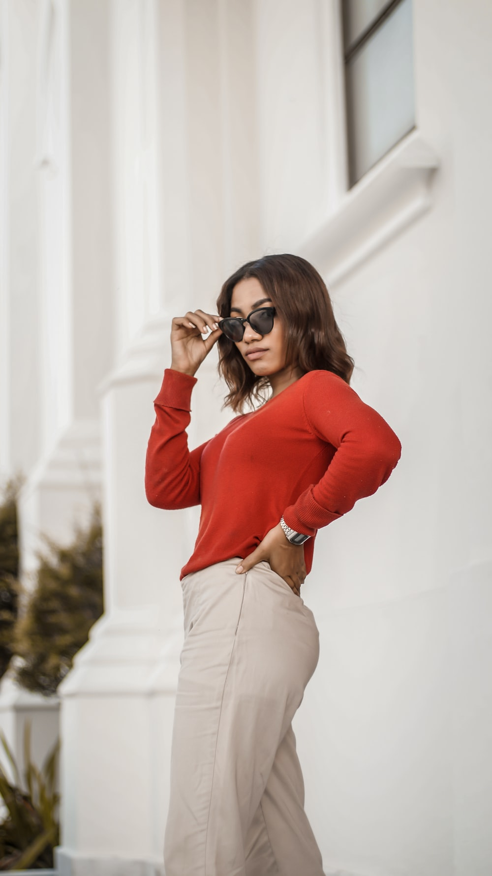 woman in red long sleeve shirt and beige pants wearing black sunglasses
