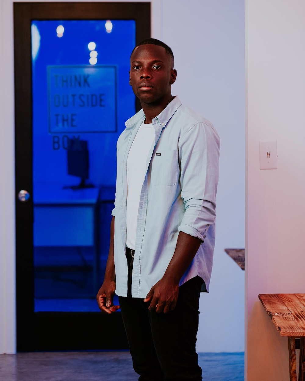 man in white dress shirt and black pants standing near blue door