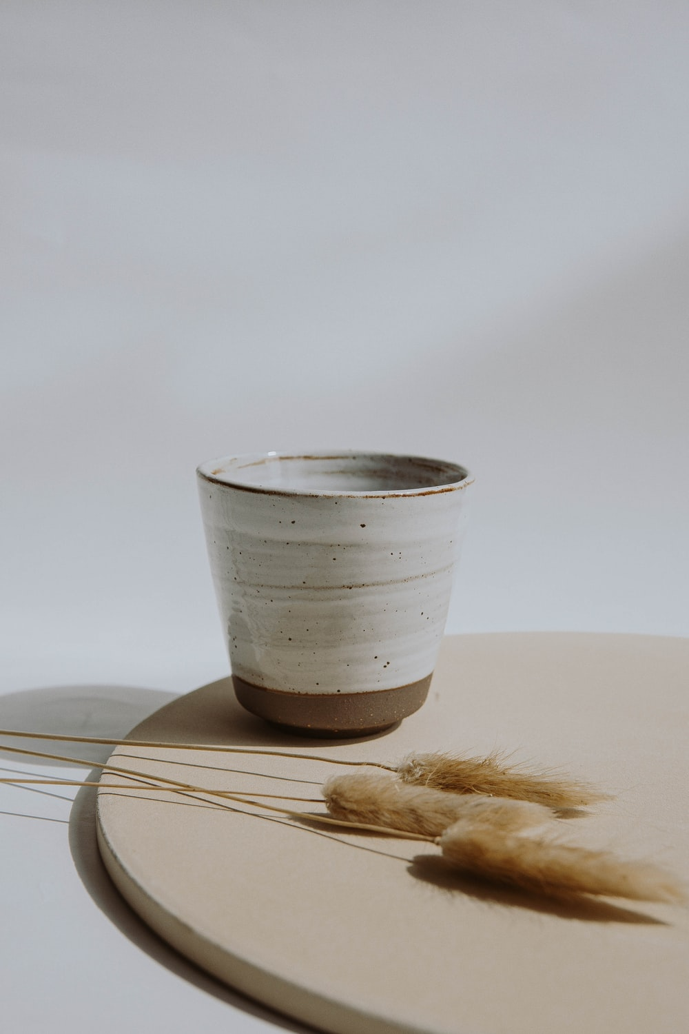 white and silver cup on brown wooden table