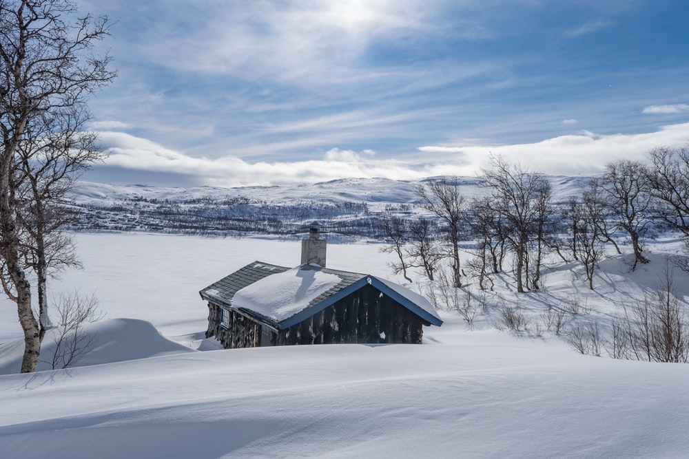 brown wooden house on snow covered ground under white clouds and blue sky during daytime