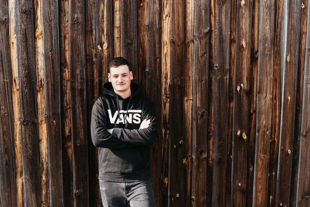 man in black and white hoodie and blue denim jeans leaning on brown wooden wall