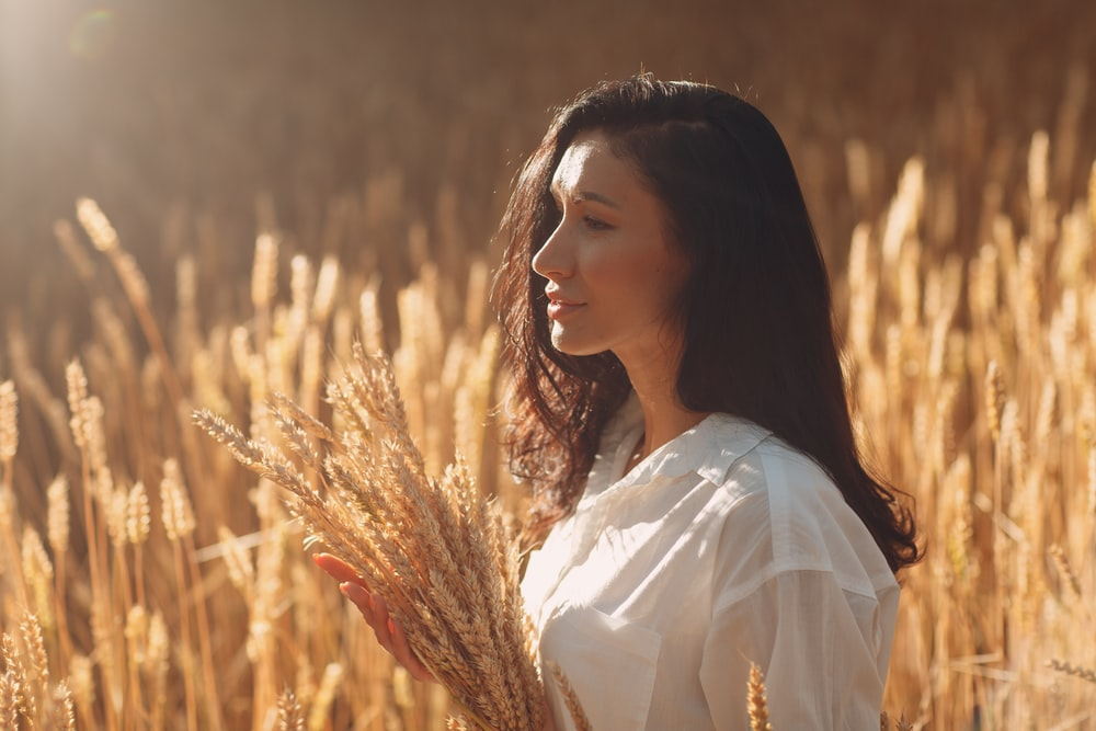 woman in white shirt standing on brown grass field during daytime