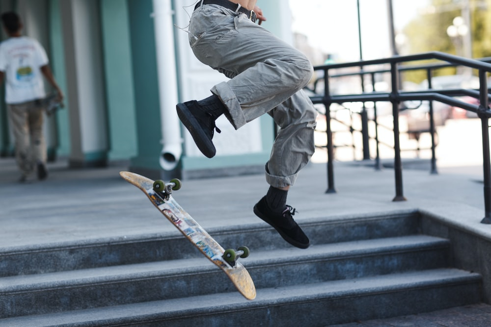 man in gray pants and black shoes riding skateboard