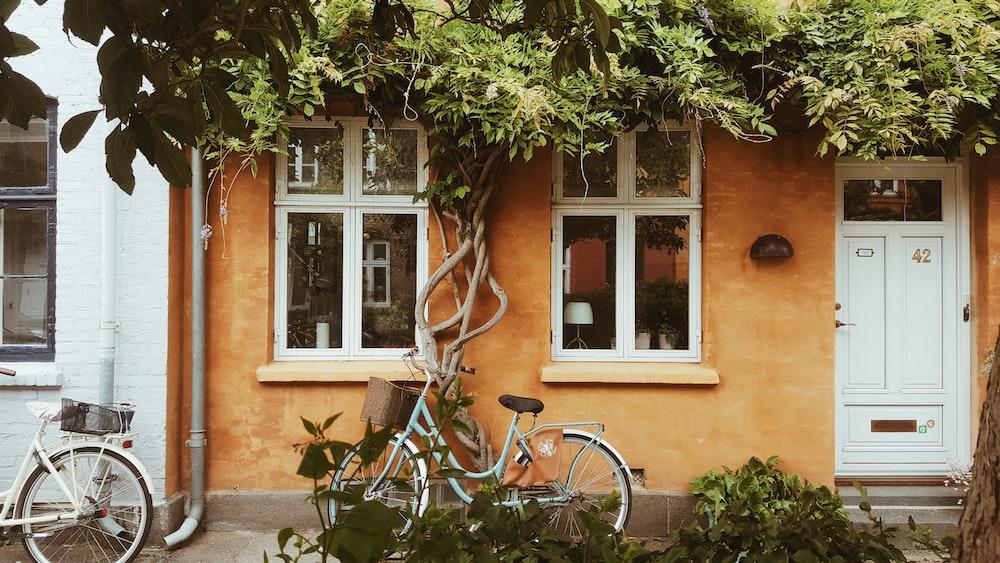 blue city bike parked beside brown concrete building