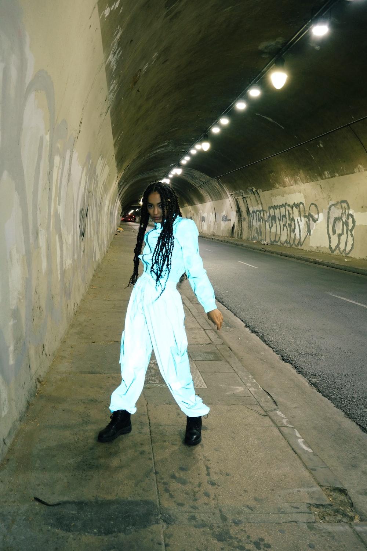 girl in white pajama set standing on gray concrete floor