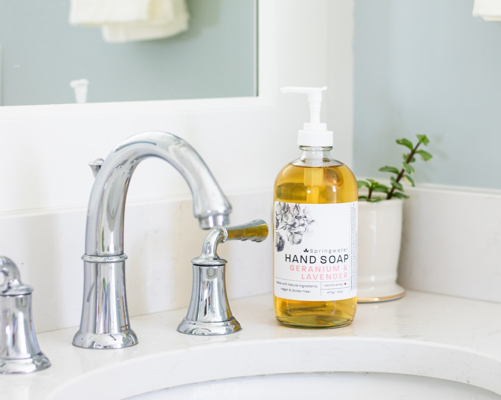 white and yellow plastic pump bottle on white ceramic sink
