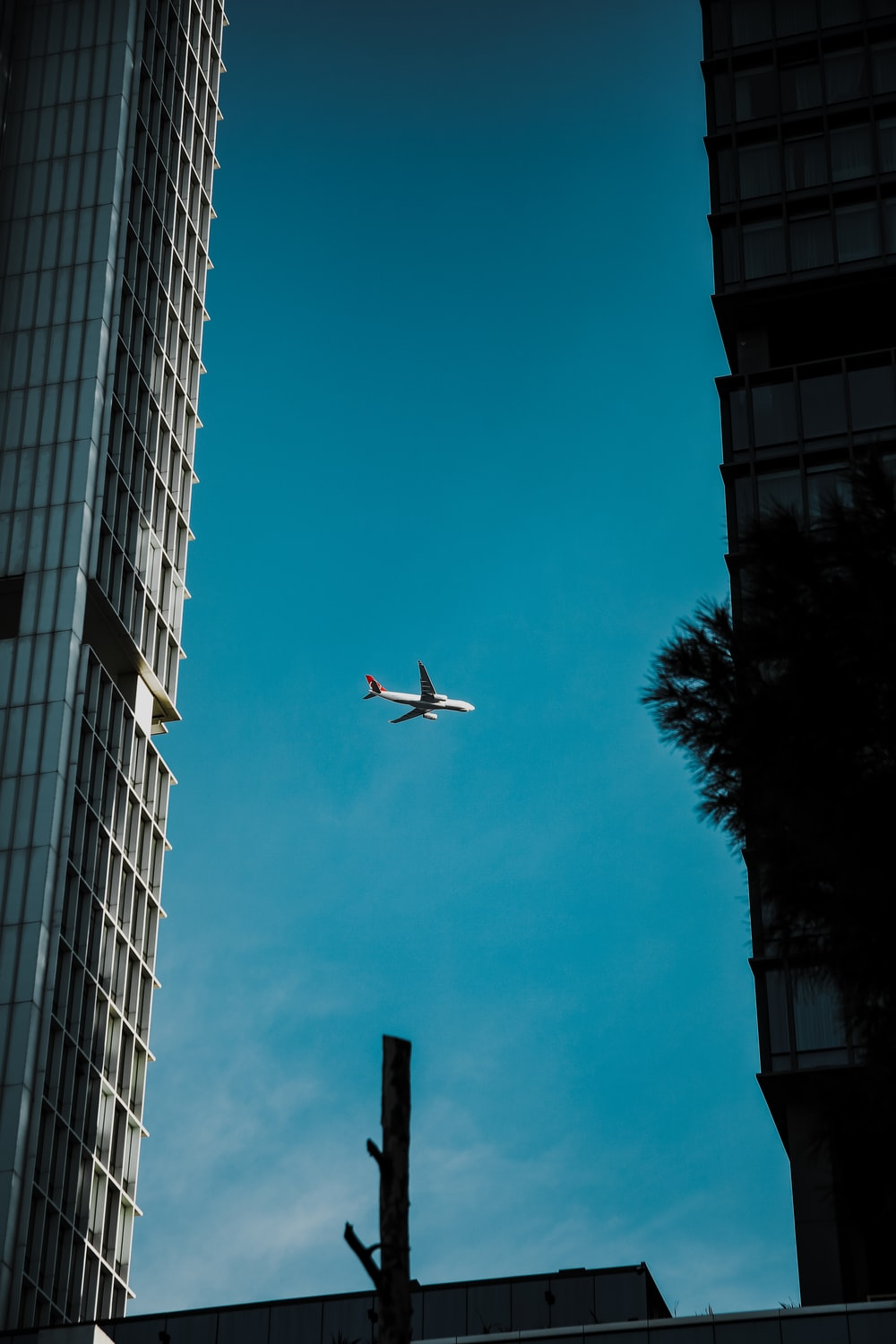 white airplane flying over the building during daytime